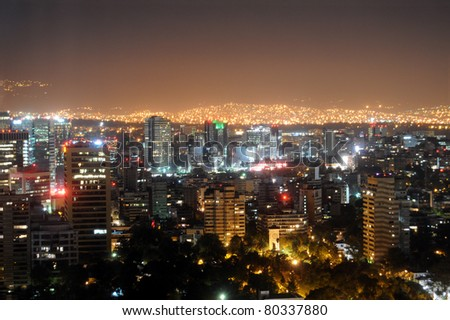 Downtown Mexico City skyline at night, with brightly lit suburban barrios in the background