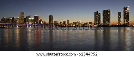 Downtown Miami Skyline Panorama with Biscayne Bay and reflecting lights on the bay.