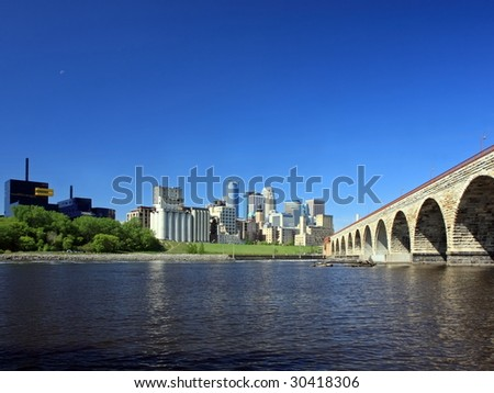 Downtown Minneapolis and Stone Arch bridge over Mississippi river