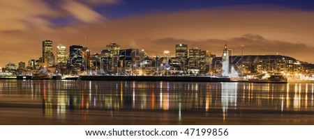 downtown panorama skyline  at dusk cityscape night scene Montreal Canada over river Saint Lawrence impressive and vibrant dusk sky skyscrapers lights reflecting on water surface typical american city
