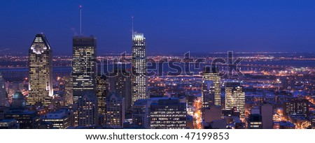 downtown panorama skyline montreal at dusk cityscape with skyscrapers lights on and saint lawrence river and bridge and suburban area in background, the lights are reflecting on the river surface