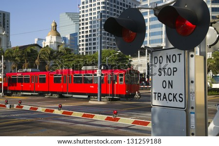 Downtown Scene at RailRoad Crossing Red Trolley Car Passing Signal Lights with Buildings in the Background