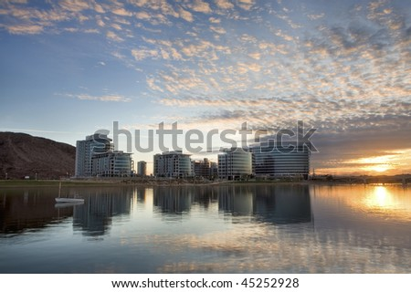 Downtown Tempe office and condo buildings with Tempe Town Lake in the foreground and a fishing boat at sunset.