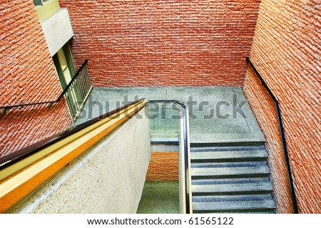 Downward perspective on staircase in a building made of orange red bricks, different materials on all surfaces.