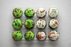 Dozen cupcakes in clear packaging decorated for Christmas