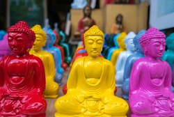 Dozens of colored small statues of Buddhas displayed on tourist stall shop in the art and craft market in Ubud. Indonesia