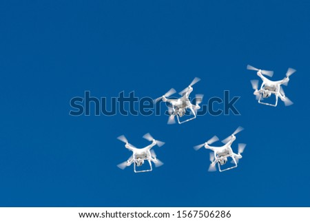 Dozens of drones swarm in the blue sky. Quadcopters drones with digital camera in the air over city. New technology in the aero photo shooting and filming. Copyspace for text