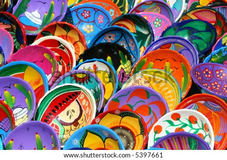 Dozens of handmade bowls are arranged neatly on tables in Chichen Itza Mexico. They are beautifully painted with vibrant colors and unique designs.