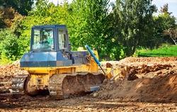Dozer at construction works, heavy duty bulldozer leveling ground. Heavy machinery, level ground. Crawler dozer at construction site, rear view