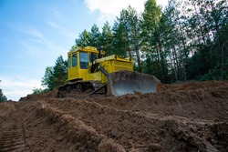 Dozer during clearing forest for construction new road . Yellow Bulldozer at forestry work Earth-moving equipment at road work, land clearing, grading, pool excavation, utility trenching
