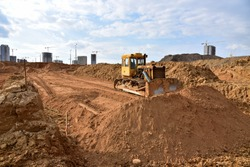 Dozer during roadwork at construction site. Bulldozer for land clearing, grading, pool excavation, utility trenching and foundation digging. Heavy machinery for earth-moving