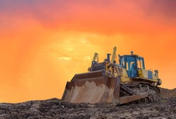 Dozer on earthmoving at construction site on sunset background. Construction machinery and equipment on groundwork. Bulldozer leveling ground in open pit. Mining industry concept