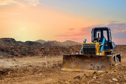 Dozer on land clearing, grading, pool excavation, utility trenching. Earth-moving equipment. Bulldozer at road construction on sunset background. Leveling ground in open pit. Mining industry concept