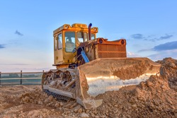 Dozer working at construction site. Bulldozer for land clearing, grading, pool excavation, utility trenching and foundation digging. Crawler tractor and earth-moving equipment