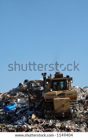 Dozer working waste at landfill