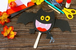 Dracola bat toy Halloween on a wooden table. Children's art project, craft for children. Craft for kids.