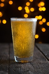 draft beer in a glass on dark blurry lights