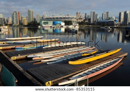 Dragon Boats on a dock in the foreground of an early morning view of downtown Vancouver reflected in the still waters of False Creek. British Columbia, Canada.