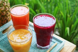 Dragon fruit, papaya and mango smoothies in glasses with bamboo drinking straws and fresh tropical fruits  outdoor