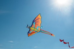 dragon - Kite flying in blue sky with sun rays in sky above it