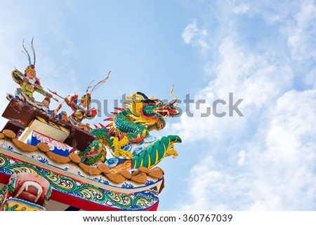 Dragon Statue on Chinese Temple Roof in Thailand with Blue Sky Background