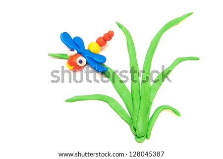 Dragonfly on grass, clay (plasticine) modeling isolated on white background.
