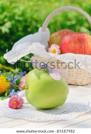 Dragonfly sits on green apple on white garden table in sunny summer day