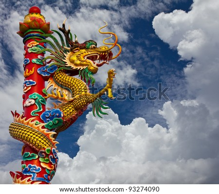 Dragons climb the pole. Golden Dragon statue, climb towers under the sky.