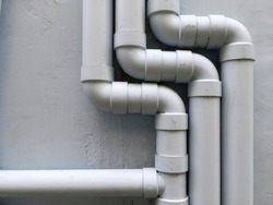 Drain pipe on gray building's wall