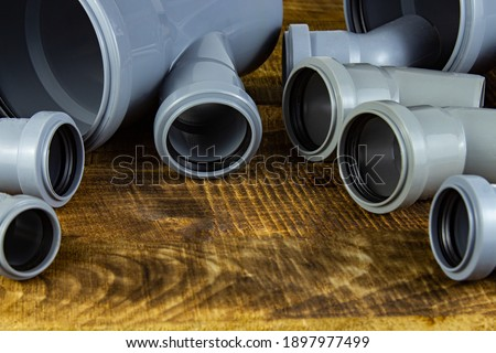 Drain Pipes. Assorted rebar gutters on wooden background stock photo