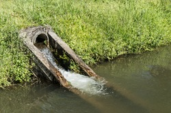 Drain water in canal : The concrete circular run-off pipe discharging water.