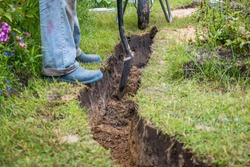 Drainage ditch. A man is digging a ditch. Laying a drainage pipe. Earthwork.