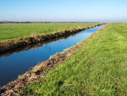 Drainage ditch and rural farmland in polder Eempolder near town of Eemnes, Utrecht, Netherlands