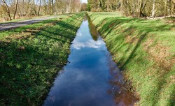 Drainage ditch to drain the moor area, with embankments with grass