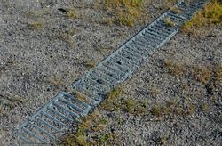 Drainage of the path by means of a gutter under which water flows. the gutter is covered with a metal grid. grassy area with paths on the slope