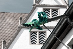Drainage pipe in the shape of a dragon under the roof of the historic old castle, Roth, Germany.