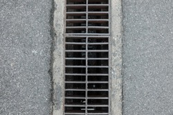 Drainage system with cement road as outdoor background. Concrete sidewalk with block metal drain Sewerage. Grid line from steel texture. grunge surface road. Rough material ground. sunlight backdrop