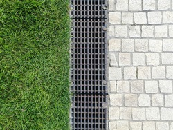drainage systems. metal structures for water drainage - sewerage and grate on the ground close-up. house construction, storm cranes. green grass and paving stones. landscaping and trellis on the groun