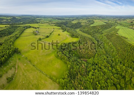 Dramatic aerial view of idyllic rolling patchwork farmland with pretty wooded boundaries, lit in warm early evening sunshine in the heart of the Cotswolds, England, UK.