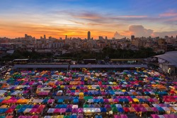 Dramatic after sunset sky over city downtown colourful night market aerial view