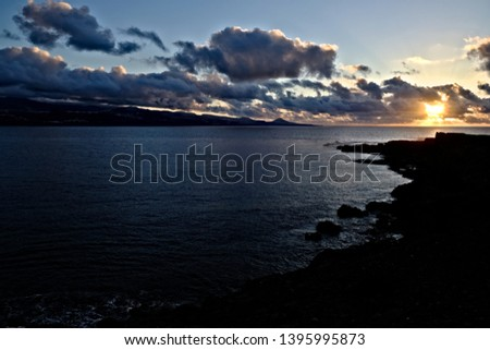 Dramatic and contrasty marine sunset over the bay of a small island.  #1395995873