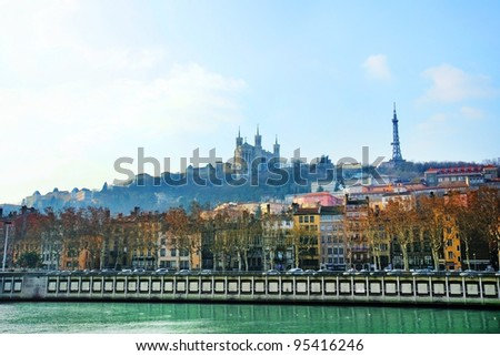 Dramatic and scenic sunrise over the river Saone in Lyon, France, with the Notre-Dame de Fourviere basilica and eiffel tower replica in the misty morning background.