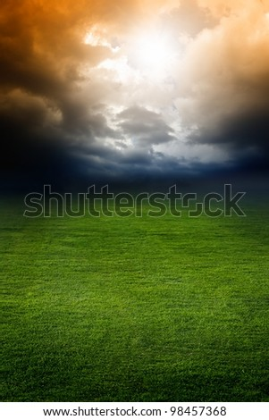Dramatic background - dark stormy sky, green field, bright light from above