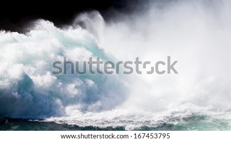 Dramatic background image of crashing wall of flood water stream breaking with flying spray
