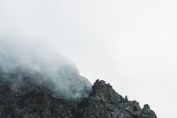Dramatic bleak fog among giant rocky mountains. Ghostly atmospheric view to big cliff in cloudy sky. Low clouds and beautiful rockies. Minimalist scenery in mysterious place at early foggy morning.