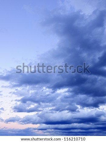 Dramatic blue cloudy formations in sky at sunset