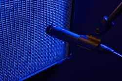 Dramatic Blue Stage Light Illuminates a Dynamic Style Microphone Placed in Front of a Vintage Guitar Amplifier