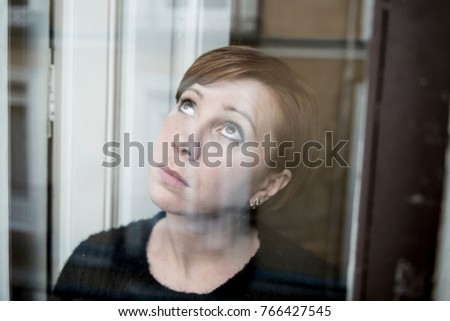 dramatic close up portrait of young beautiful woman thinking and  feeling sad suffering depression at home window looking depressed and worried in lifestyle and life problems concept #766427545