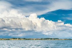 Dramatic cloud scape with windwheels on the Danmark coast of Flensburg Fjord near Sonderburg, Baltic sea, Danmark and Germany