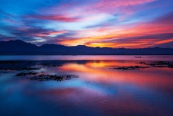 Dramatic clouds and sunset sky over the lake and mountain range in backgrounds, colourful clouds reflecting on surface of water, fisherman on fishing boat in the lake. Phayao Lake, Thailand.